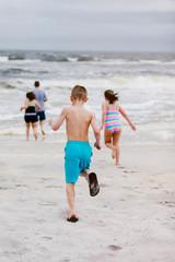 Man and children running toward sea from beach, rear view, Dauphin Island, Alabama, USA