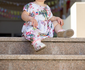 Little girl is sitting on the steps
