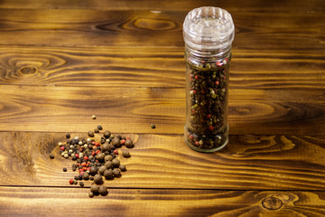 Glass pepper shaker with mix of peppercorn on wooden background