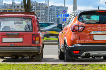 Rear view of two cars of different eras standing side by side in the city. The concept of...