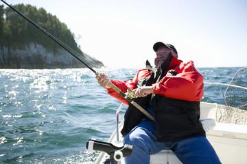 Mature adult man sitting on a boat fishing.