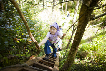 Young girl climbing a ladder in a forest.