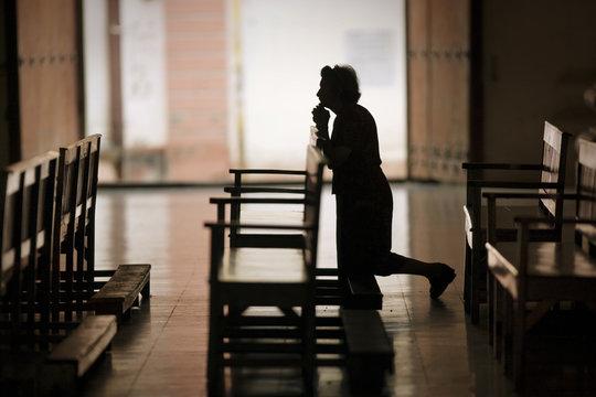 Silhouette of woman praying in church