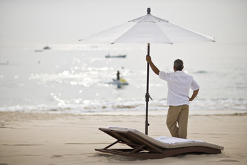 Man standing under sun umbrella looking out at the ocean