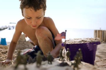 Boy building sandcastles and playing with toys on beach