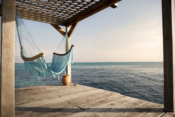 Empty hammock hanging at the edge of a wooden jetty overlooking the sea.
