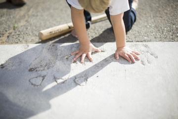 Little boy putting his hand in handprints made in concrete