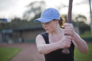 Woman preparing to bat while playing baseball