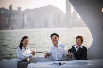 Portrait of three happy friends enjoying a glass of wine while on a boat.
