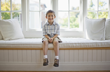 Portrait of a smiling young boy sitting on a window seat.
