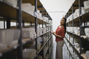 Businesswoman counting stock in a store room
