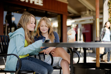 Two teenage girls looking at a cell phone and smiling while at a cafe