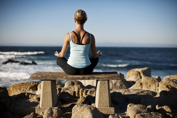 Woman doing yoga on bench by the ocean