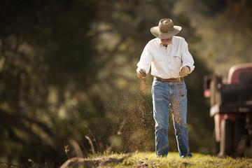 Farmer sprinkling fertiliser on grass.