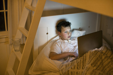 A boy using a laptop in bed at night.