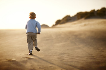 Boy running along a beach at sunset.