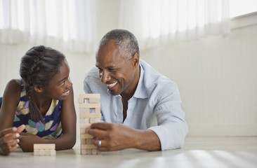 Smiling father and daughter playing with a block removal game.