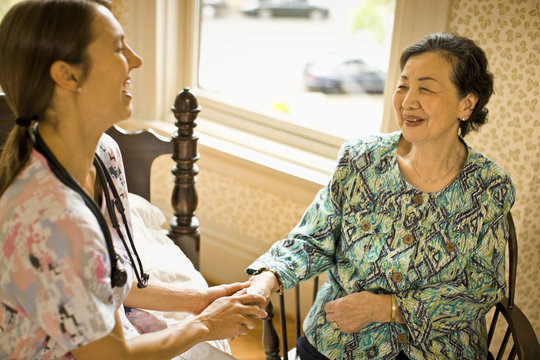 Female nurse smiles and holds the hand of a senior woman.