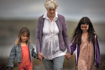 Senior woman walking hand in hand with her two granddaughters.