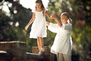 Grandmother helps her granddaughter balance across a brick fence.