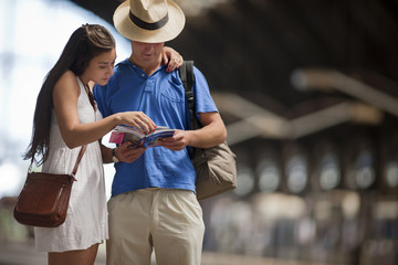 Twenty Something couple read a guide book while on vacation.