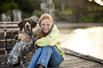 Smiling teenage girl sitting and hugging her dog on the pier.