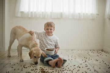Young boy sitting on floor covered in dog biscuits with his dog.