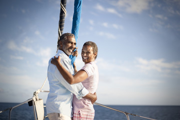 Portrait of smiling mature couple hugging on boat deck.