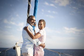 Portrait of smiling mature couple hugging on boat deck.