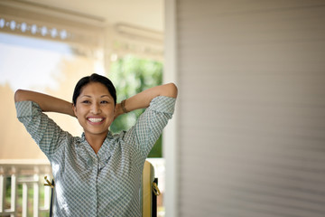 Portrait of smiling mid-adult woman standing on the porch of the house.