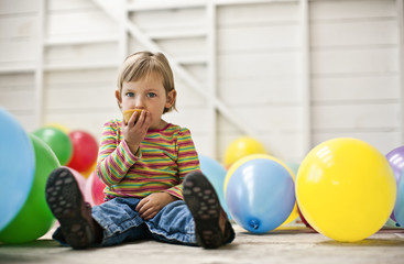 Little girl sitting in a room full of balloons and eating a cupcake.