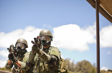Two police officers pointing a gun towards a target during training