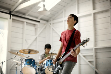 Two teenage males having a jam session on an electric guitar and drums.