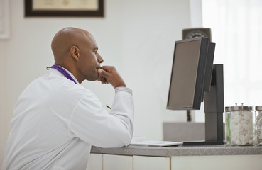 Contemplative male doctor sitting with his hand on his chin at his desk inside his office.