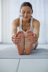 Happy young woman stretching her legs while practicing yoga