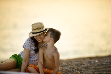 Boy kisses his mother's cheek  on the beach at sunset.