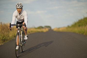 Happy mature woman cycling along a country road.