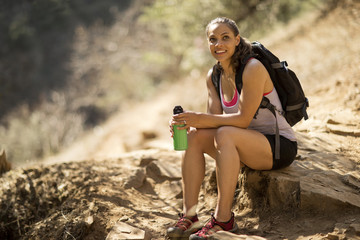 Smiling young woman taking a break from hiking.
