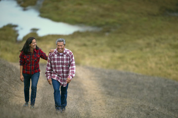 Mature couple walking on a grassy path.