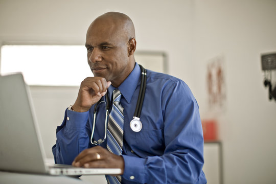 Focused middle aged doctor working on a laptop in his office.