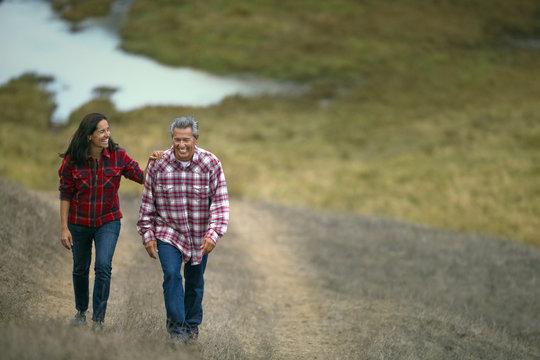 Mature couple walking on a grassy path.