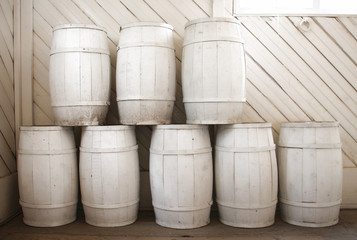 Pile of white painted barrels insite a white wooden room