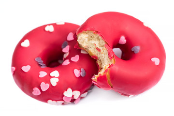 Bited Donuts with heart sprinkles isolated on background close up.