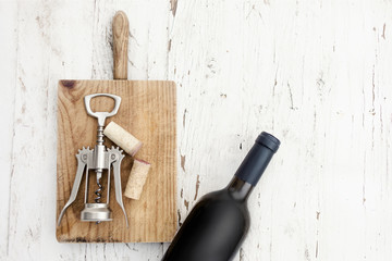 Bottle of Red wine, corkscrew  and wine corks on rustic white wooden background, copyspsce. Wine tasting concept.