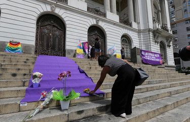 A demonstrator places flowers before the wake of councilwoman Marielle Franco, 38, who was shot dead, in Rio de Janeiro