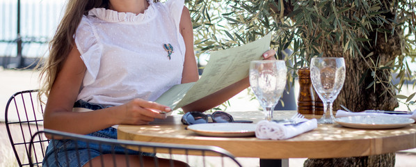 A woman is studying drawings and schemes in a cafe