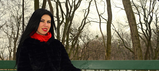 Portrait of brunette girl in fur coat and scarf on winter forest background.