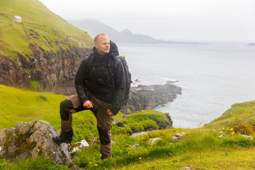 Hiker Standing in the rain On Mountain at Faroe Island With Sea In Background