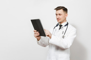 Confident experienced handsome young doctor man isolated on white background. Male doctor in medical uniform, stethoscope holding tablet pc computer. Healthcare personnel, health, medicine concept.