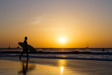 Beach sunset with silhouetted surfer